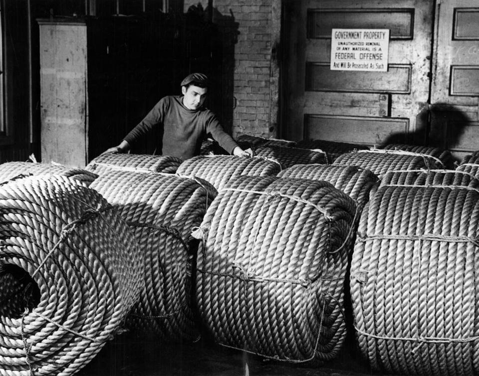 BOSTON, MA : Angelo Nastrangello checks rolls of six-inch rope, ready for shipment to Naval bases for use aboard fleet ships at the Ropewalk in the Charlestown Navy Yard in Boston. This rope has minimum breaking strength of 31,000 pounds, weighs over a pound per foot. (Metro Group Editorial Service) --- BGPA Reference: 160519_MJ_010