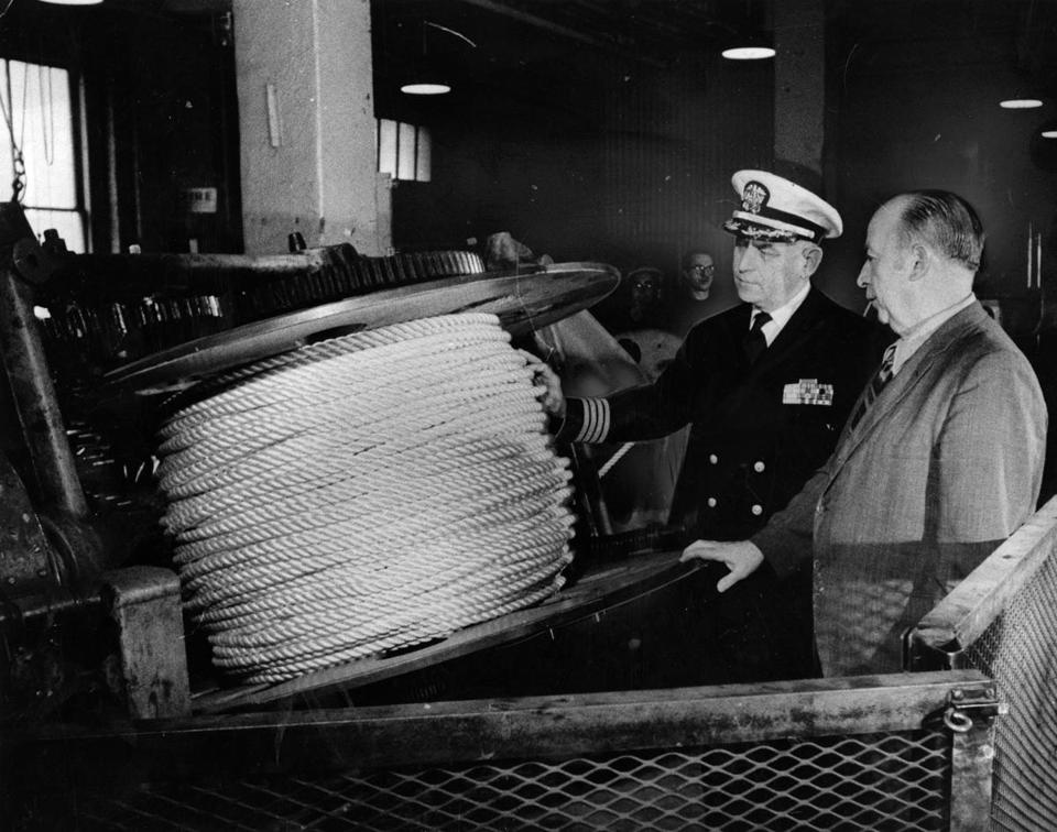BOSTON, MA - 12/17/1971: Capt. Raymond W. Burke, commandant of the Boston Naval Shipyard, and Edmust Skelly, general foreman of the yard's historic Ropewalk, inspects last coil of rope to be produced at the Ropewalk complex in the Charlestown Navy Yard in Boston Dec. 17, 1971. The Navy Department has ordered ropewalk closed at the end of the month after 137 years of operation and will buy rope from commercial firms. (Ed Farrand/Globe Staff) --- BGPA Reference: 160519_MJ_014
