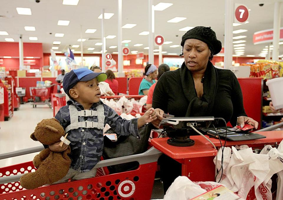Colleen Michell, with her son Hanson, struggled with her chip card at a Target store in Dorchester. The cards represent a step up for security and a step down for efficiency.