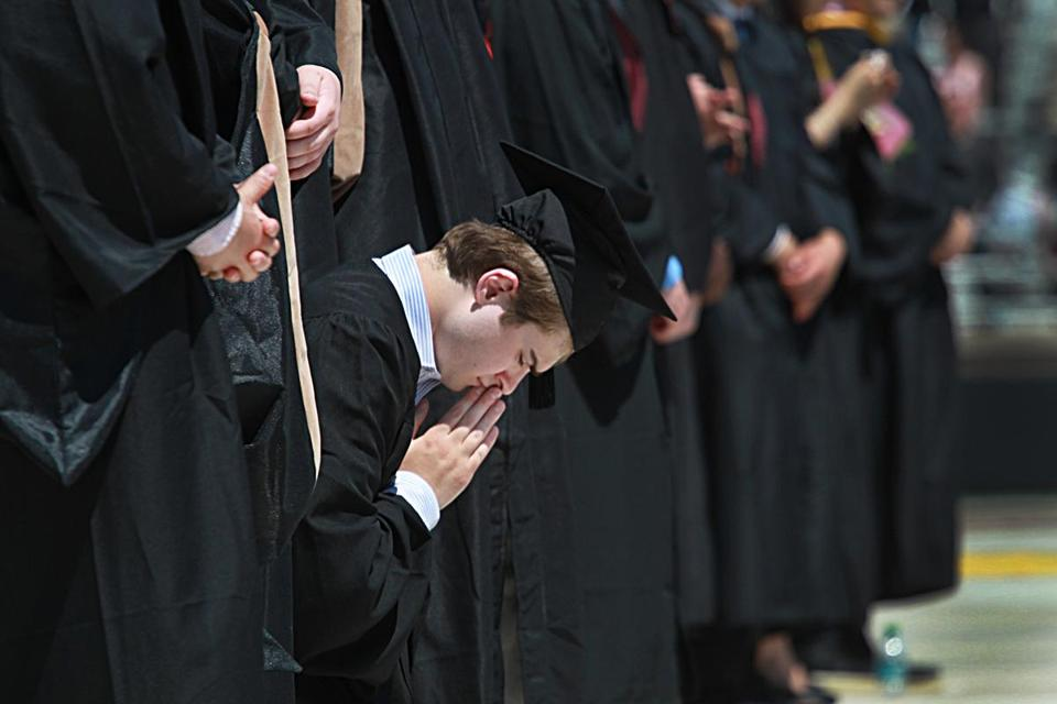 Students prayed at the end of BC's commencement ceremony.