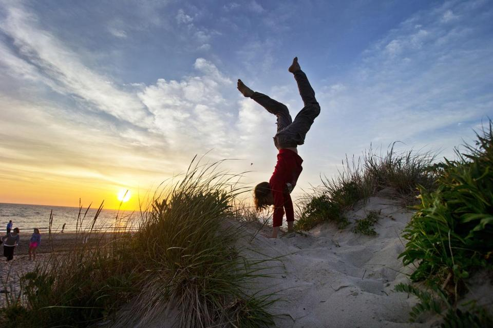 "Wellfleet, MA- July 1, 2014- Globe Staff Photo by Stan Grossfeld- Damon Wolf, 13, New Paltz, N.Y. does a handstand as the sun sets into Cape Cod Bay in Wellfleet.Damon Wolf, 13, New Paltz, N.Y. ""The sun kind of got low enough in the sky and it just illuminated everything and the colors of the dunes were really saturated and really popped out at me and looked awesome. It just made me extremely happy. I love life, life is awesome. This is such a beautiful place to be in the entire world. Seeing the sun and looking out over the ocean and its just endless power it just makes everything look surreal and amazing and beautiful."""