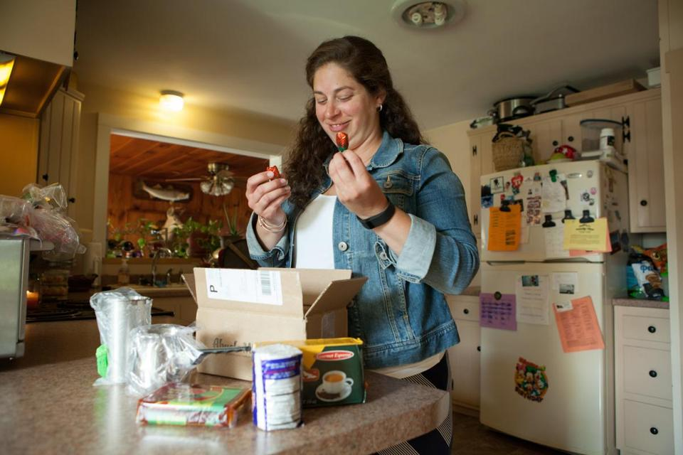 Kristen Gonzalez of Northfield opening her monthly package from Abuela Mami.