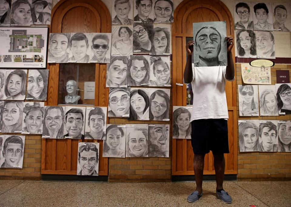 Senior Phillip Sossou 18, held lds his self-portrait while posing with his artwork at Boston Latin School.