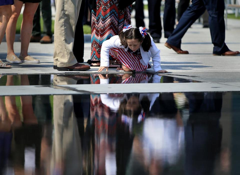 Boston Ma 0527 2016 Skylah Sherman (cq) age 6 blows onto water at the base of the new Massachusetts Fallen Heroes Memorial in the Seaport District.She is wearing her father Army Sgt. Benjamin W. Sherman Dog Tags while at dedication ceremony. Her father was killed while serving Iraq. She is from Plymouth Massachusetts.Globe/Staff Photographer Jonathan Wiggs