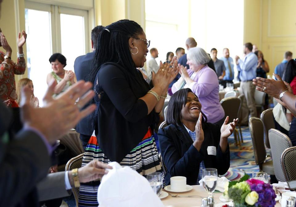 Natalia Phillip (right), valedictorian of New Mission High School, laughed as her sister, Janel Alfred, applauded her and her fellow valedictorians during a luncheon at the Boston Harbor Hotel.