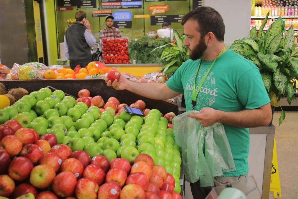 Boston, MA - 06/1/15 - A company called Instacart sends people into stores like Whole Foods to fulfill grocery delivery orders from other people. Owen Amsler (cq), an Instacart shift captain, shops for a customer in the Whole Foods Market South End. Lane Turner/Globe Staff Section: BIZ Reporter: curt woodward Slug: 12betaondemand