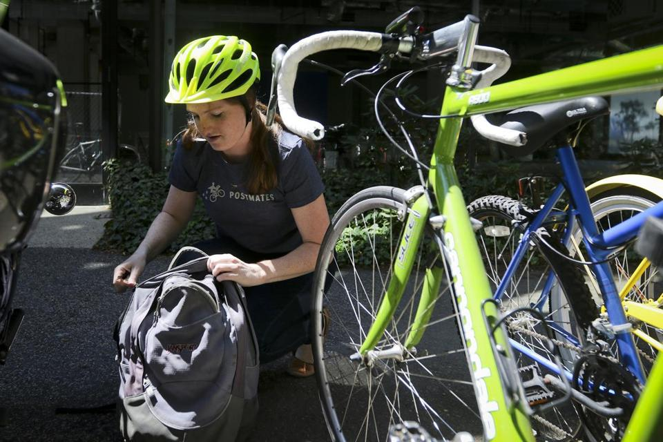 "Cambridge, MA - 8/14/2015: Postmates employee Margaret Purdy of Somerville, MA prepares to make a delivery on Aug 14, 2015. Purdy heard about the job while browsing online, and had been working for postdates for around two months. ""I have gotten the chance to meet other people through it, which is cool,"" said Purdy. (Harrison Hill for The Boston Globe)"