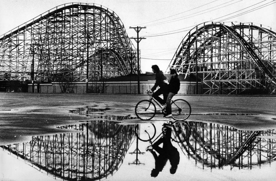 Hull, MA - 3/24/1984: Kelley McLaughlin, 13, and Ann Nigro, 14, of Hull, ride past the roller coaster at Paragon Park in Hull, Mass., on their way home from school on March 24, 1984. (Stan Grossfeld/Globe Staff) --- BGPA Reference: 150320_MJ_015
