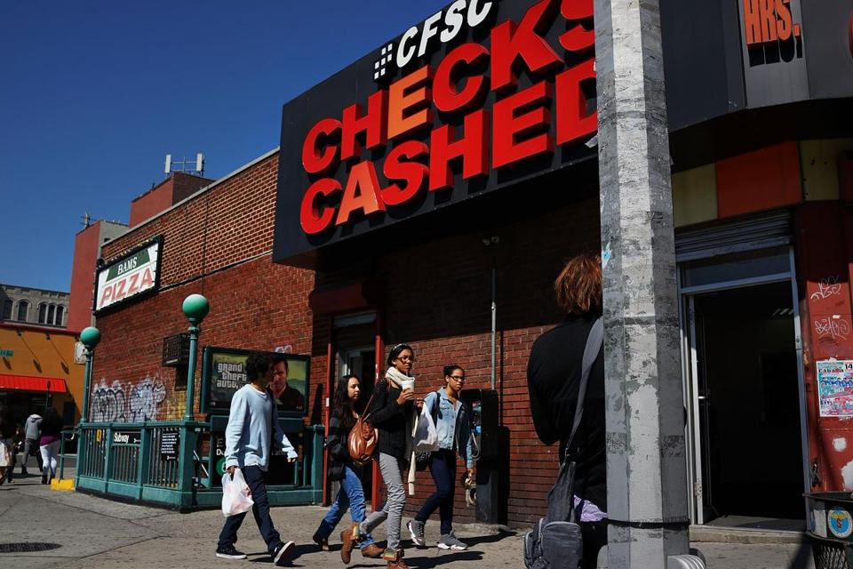"NEW YORK, NY - SEPTEMBER 19: People walk by a check cashing store in the South Bronx on September 19, 2013 in New York City. According to the 2010 U.S. Census Bureau report, over a quarter-million people in the South Bronx are living in poverty, making the 16th Congressional District the poorest in the nation. New Census Bureau numbers for all of New York City show that the poverty rate has risen to 21.2 percent in 2012, from 20.9 percent the year before. As New Yorkers prepare to vote for their next mayor following Michael Bloomberg, the Democratic candidate Bill de Blasio has focused on the theme that New York has transformed into a ""tale of two cities"" under the Bloomberg administration. (Photo by Spencer Platt/Getty Images)"
