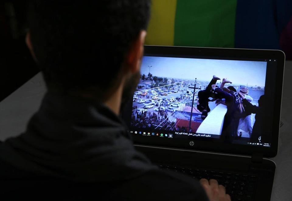 A gay Syrian, living in southern Turkey, shows a photo from his laptop, in 2015, of Islamic State group militants allegedly throwing a man off a roof for homosexuality.