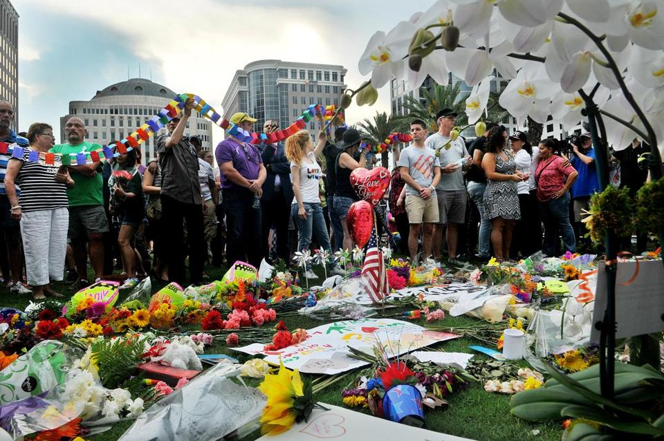 People pay respect at a memorial during a vigil honoring the victims of a mass shooting at Orlando's nightclub Pulse, as they gather at the Dr. P. Phillips Center for the Arts in Orlando, Fla., Monday, June 13, 2016. (Craig Rubadoux/Florida Today via AP) MANDATORY CREDIT