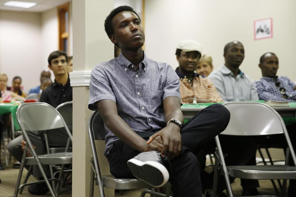 Needham, Massachusetts -- 7/16/2015-- Unable to go home for his father's funeral in Burundi, Alex listens to a sermon during a Memorial Service for his father at at Good Shepard Christian Fellowship in Needham, Massachusetts September 19, 2015 just four months after celebrating Leo's 5th birthday in the same location. Jessica Rinaldi/Globe Staff Topic: 062616alexleofollow Reporter: Scott Helman