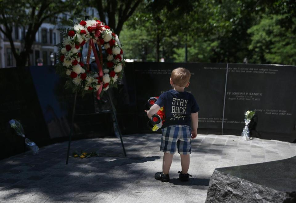 Connor Aigen, 2, of Newton, held his favorite toy firetruck while looking at the Hotel Vendome fire memorial after the ceremony.