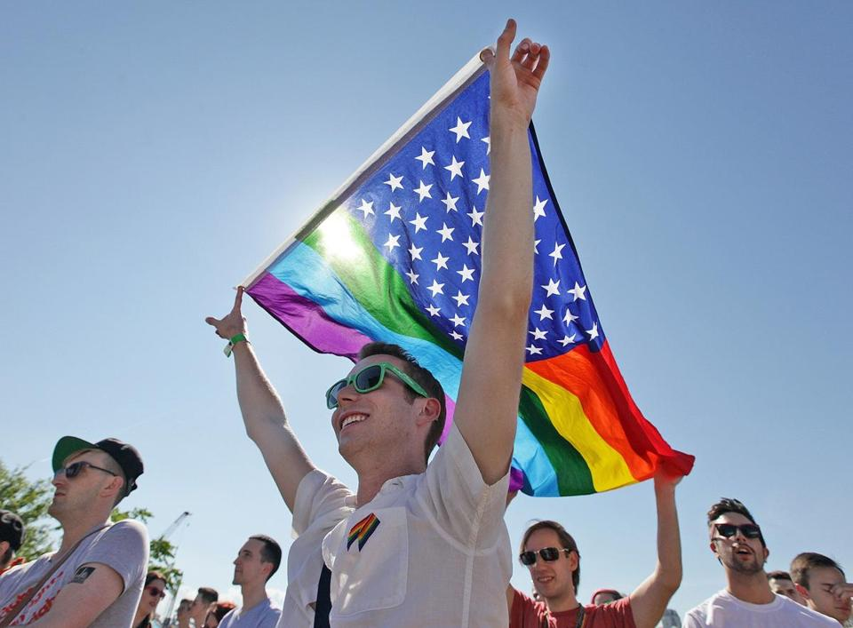 Drew Milligan (front), of Providence, and Graham Stokes, of Exeter, R.I., held a flag while listening to music at Rhode Island PrideFest in Providence Saturday.