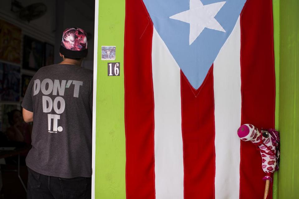A Puerto Rican flag hangs outside a community gallery in Caguas, Ruerto Rico, June 7, 2016. Puerto Ricans are sharply divided over White House-backed legislation designed to reboot their economy as they try to decide what is worse: the homegrown leaders they feel have failed them, or a federally appointed independent board that many distrust. (Erika P. Rodriguez/The New York Times)