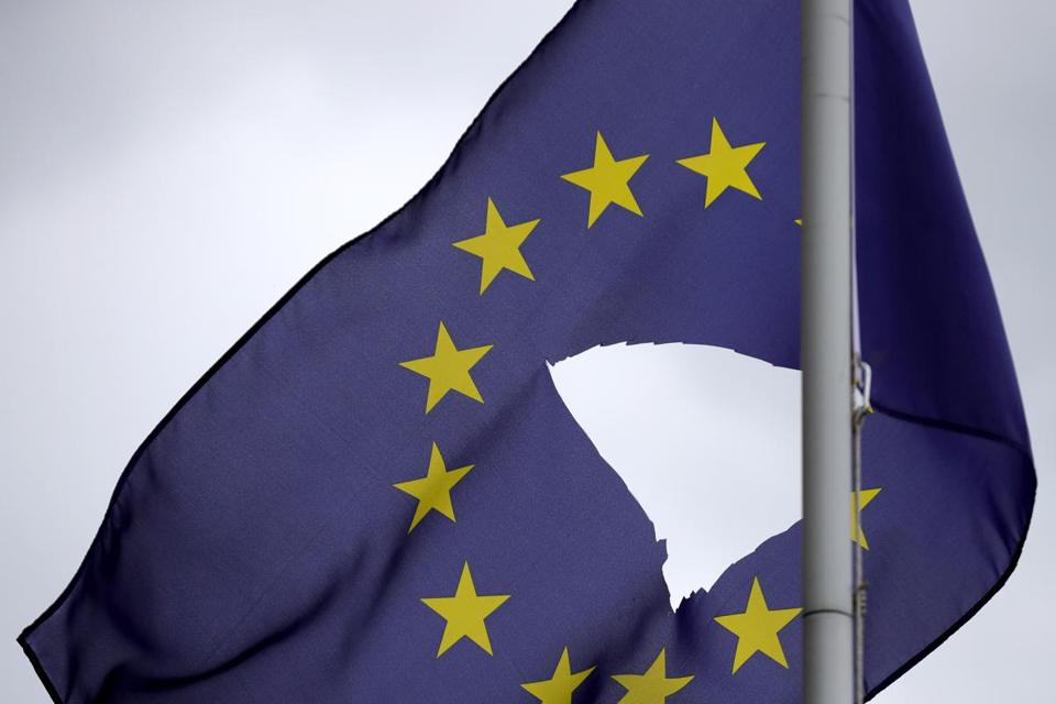 A European Union flag, with a hole cut in the middle, flies at half mast in Knutsford, England.