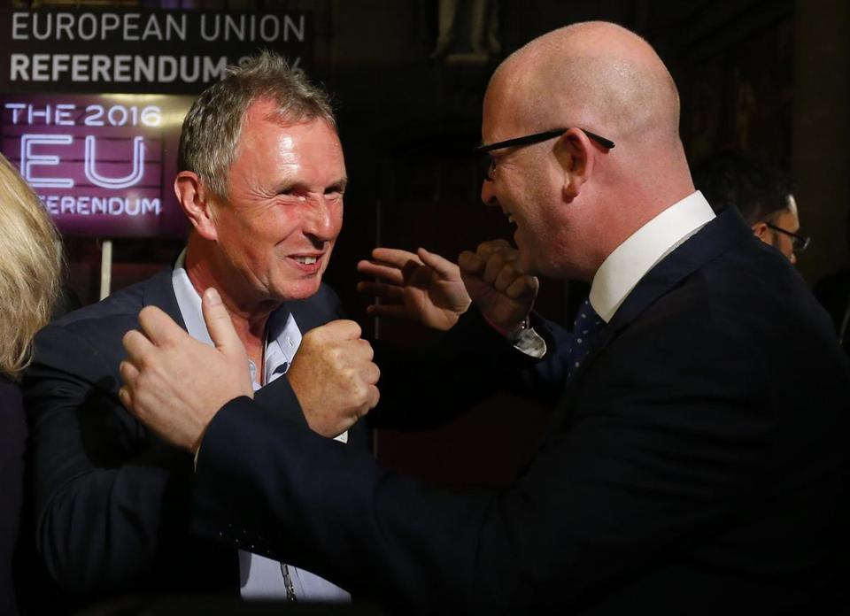 Paul Nuttall (R), United Kingdom Independence Party (UKIP), MEP for the north west of England and Nigel Evans Conservative MP for Ribble Valley celebrate the likely victory of 'Leave' in the EU referendum, at the Manchester Town Hall in Manchester, north west England on June 24, 2016. Britain's economy was plunged into a dizzying unknown on Friday as the country lurched towards the EU exit, with the world economy bracing for a hit on growth and unemployment. / AFP PHOTO / Lindsey PARNABYLINDSEY PARNABY/AFP/Getty Images
