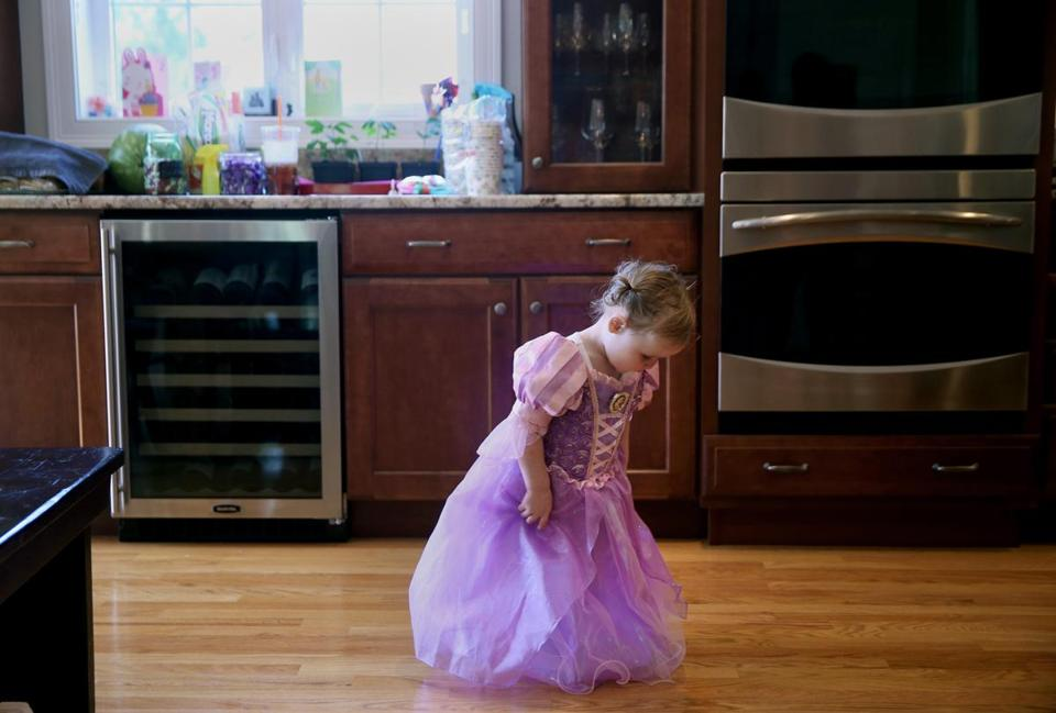 ANDOVER, MA - 6/25/2016: Emma Genest, 2, looks at her Rapunzel dress before her birthday party in Andover, Massachusetts, on Saturday, June 25, 2016. The princess-themed party included dancing, games and face painting. (Timothy Tai for The Boston Globe)