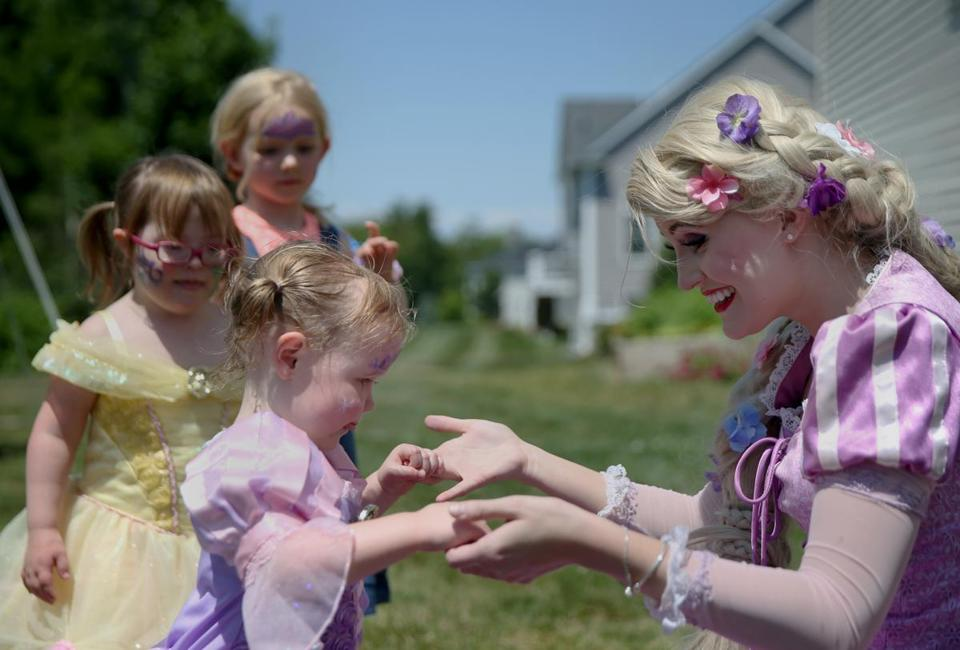 ANDOVER, MA - 6/25/2016: Catherine Busby, right, of Sterling, Massachusetts, dressed as Rapunzel, holds hands with Emma Genest, 2, also dressed as Rapunzel, during Emma's birthday party in Andover, Massachusetts, on Saturday, June 25, 2016. The princess-themed party included dancing, games and face painting. (Timothy Tai for The Boston Globe)