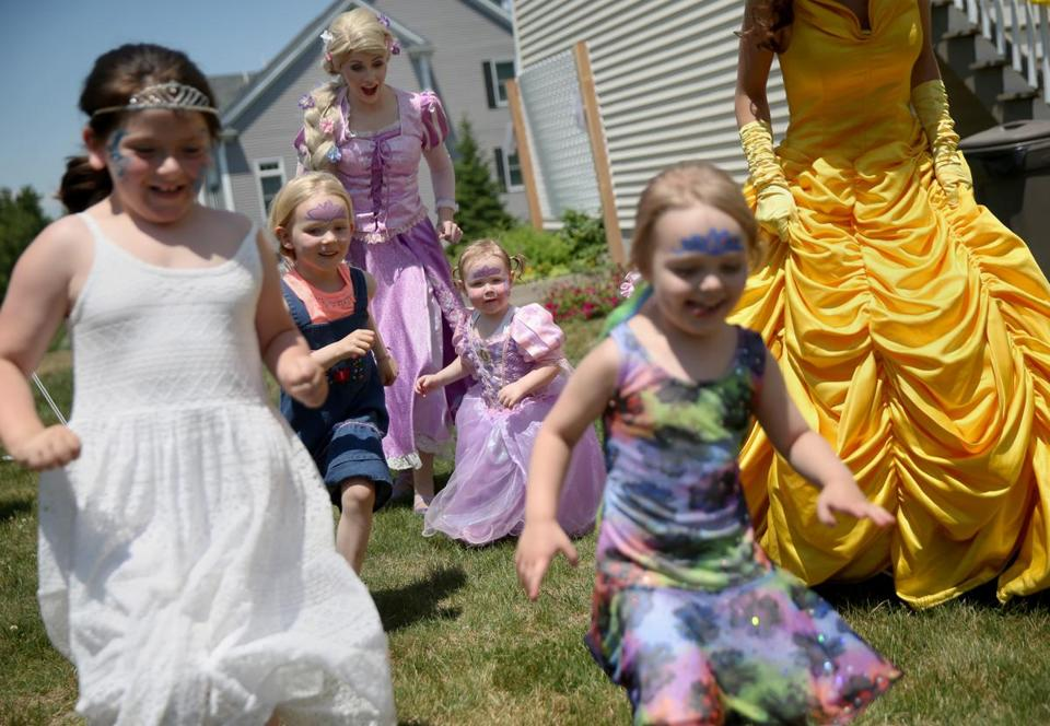 Catherine Busby (left) and Katherine Copeland (right), dressed as Rapunzel and Belle, play with guests at