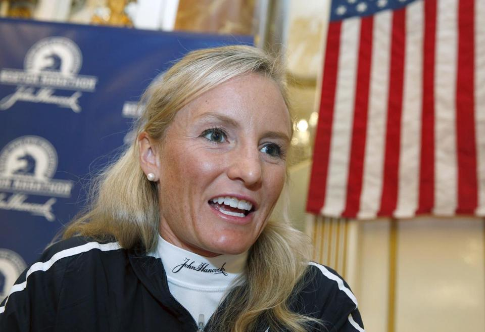 In this Friday, April 15, 2016 photo, Shalane Flanagan speaks with a reporter during a media availability prior to the 120th running of the Boston Marathon in Boston. Fifty years after Bobbi Gibb sneaked into the Boston Marathon wearing her brother's Bermuda shorts and a hoodie covering her long hair, the race celebrates a half-century of women who broke barriers and the finish-line tape. (AP Photo/Michael Dwyer)