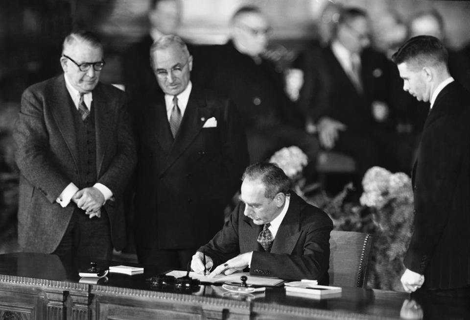 Secretary of State Dean Acheson signs the Atlantic defense treaty for the United States, April 4, 1949. Vice President Alben W. Barkley, left, and President Harry Truman converse during the signing. (AP Photo)