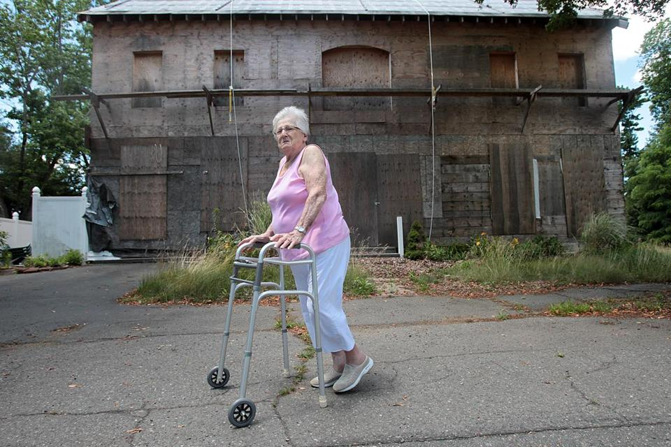 Gloria Lilja, 84, at the house that now stands gutted and boarded up in Beverly.