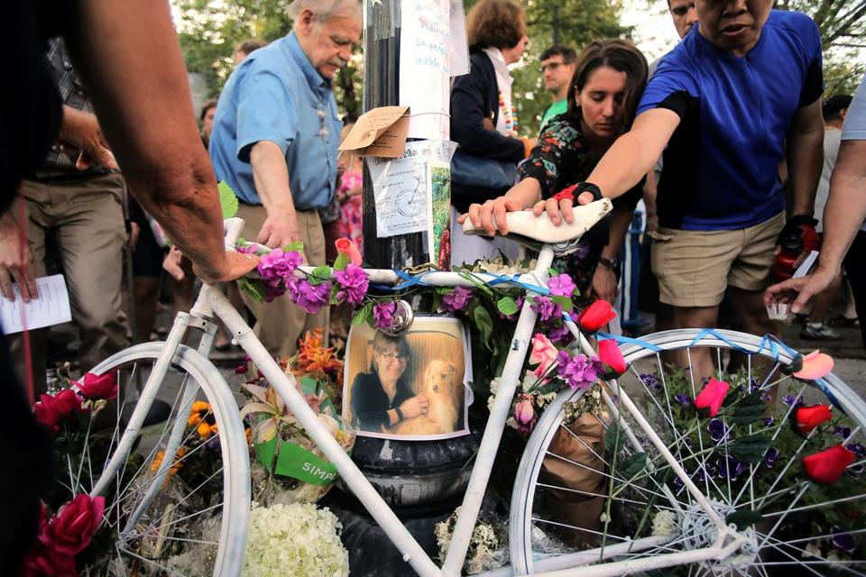 Mourners reach out to touch a ghost bike at a vigil for Amanda Phillips, who was killed while riding a bike in Inman Square.
