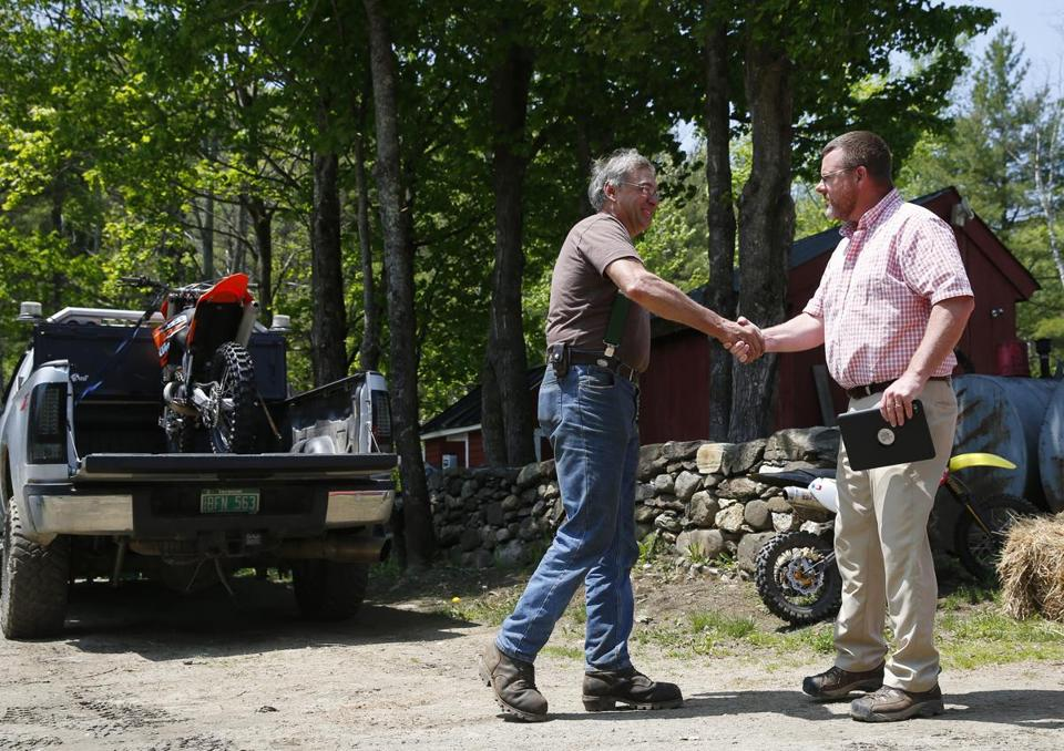 Dave Goodhouse (left) shook hands with a Caterpillar salesman who came to the Goodhouse home to assess a bulldozer that the logger was hoping to sell.