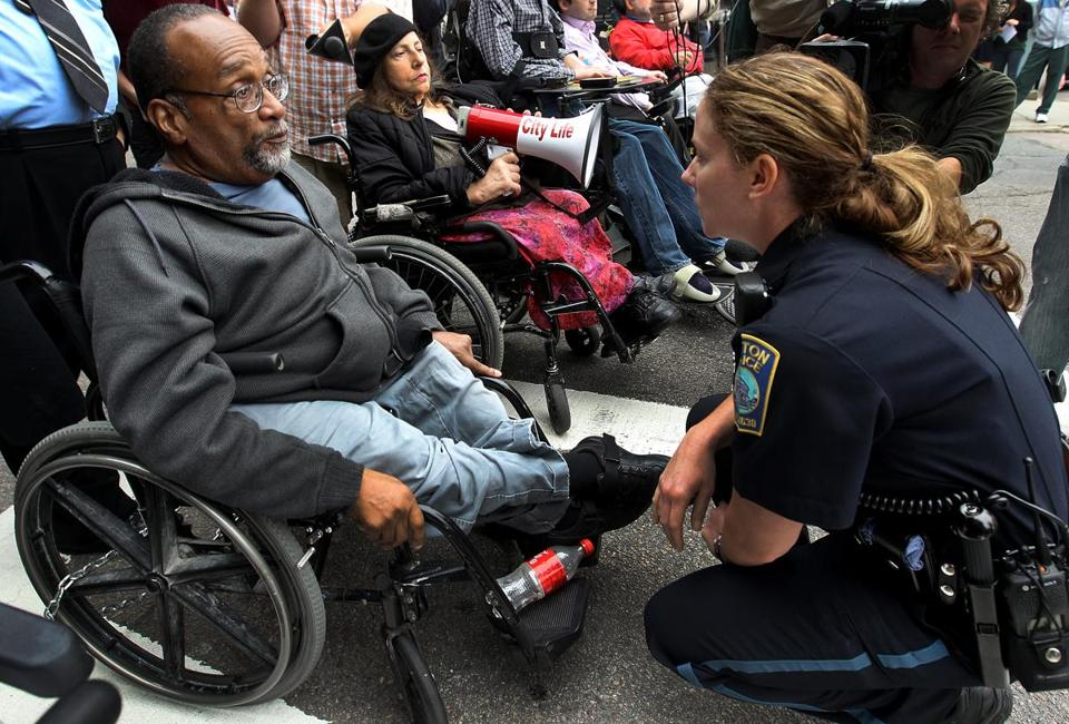 A Boston police officer spoke with Mr. Brooks on May 21, 2012, as a group gathered in front of the State House to demonstrate against fare increases for The Ride.