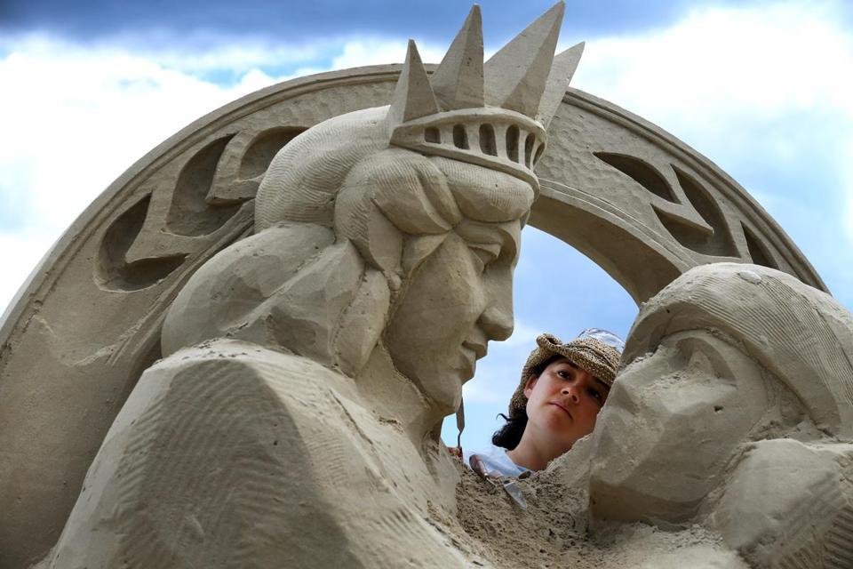 "07/24/2015 Revere, MA � Sue McGrew of Tacoma, WA, works on her sculpture during the Revere Beach International Sand Sculpting Festival in Revere, MA, on July 24, 2015. The festival is expected to draw 700,000 people through the weekend. McGrew hadn't titled the piece yet but said the work would depict, ""Lady Liberty removing the blindfold from Lady Justice.""(Craig F. Walker / Globe Staff)"