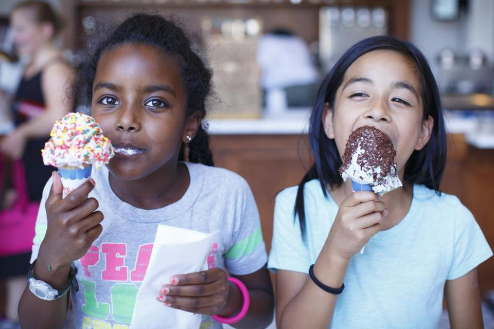 At Forge Ice Cream Bar, Lettie Carswell, 8, of Arlington enjoy a cone of strawberry with rainbow sprinkles and Clara Mapel, 8, of Cambridge a mint cookie and cream cone with chocolate sprinkles.