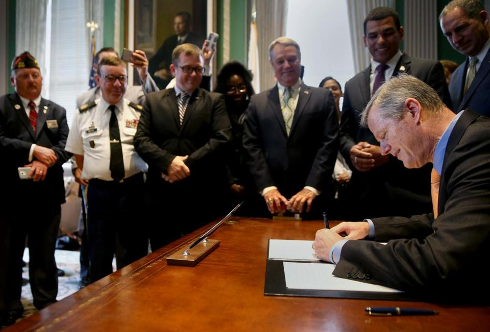 Governor Charlie Baker signs a veterans benefits bill in his office on Thursday.