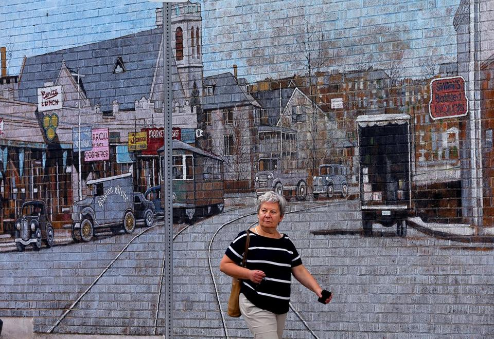 West Roxbury 5/28/2016- Location of West Roxbury. A woman walks past a mural depicting and old view of Centre Street painted on the side of a business on Hastings Street at Centre Street.Boston Globe staff photo by John Tlumacki(business)