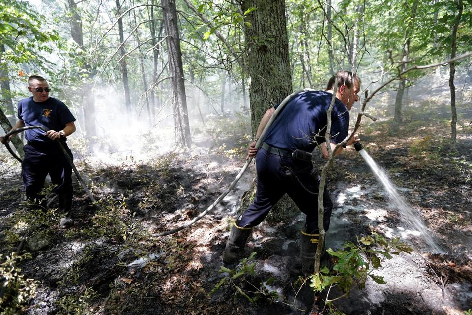 Sudbury Firefighters Kyle Gordon, at left, and Russ Place, with hose, battled a stubborn fire burning inside the Nobscot Scout Reservation that has persisted due to the dry conditions brought on by the current drought.