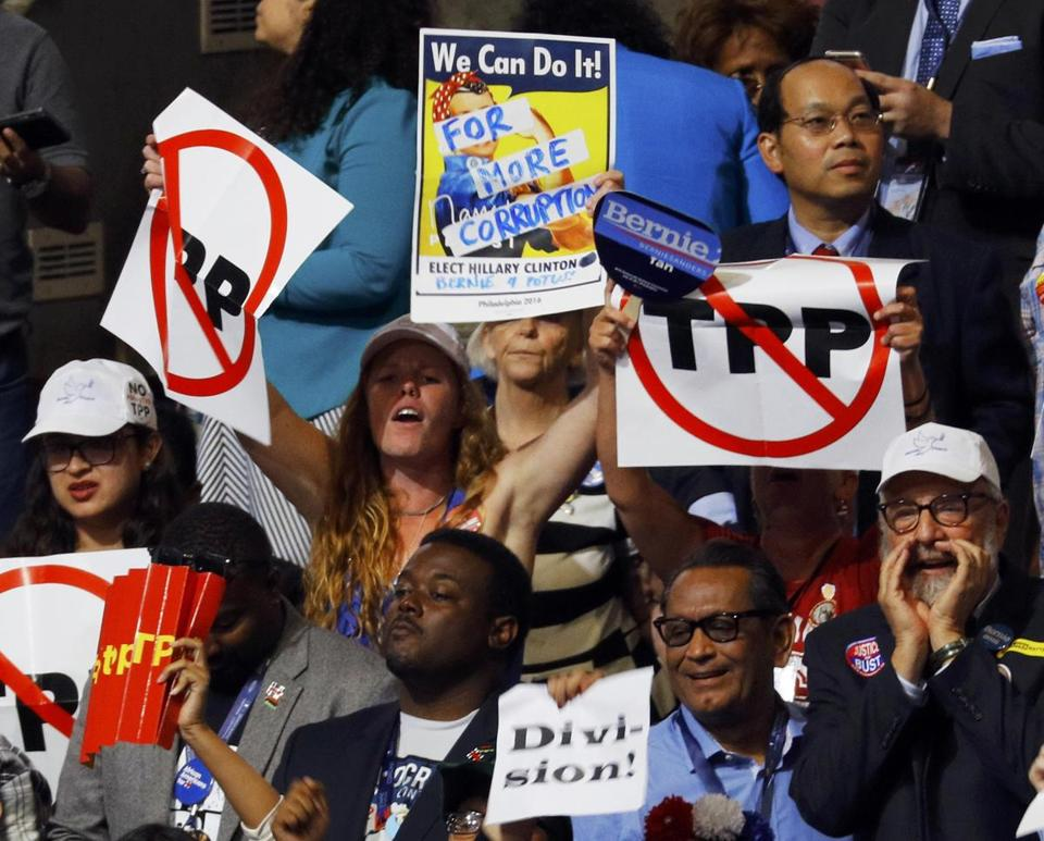 Delegates protesting against the Trans Pacific Partnership trade agreement held up signs during the first sesssion of the Democratic National Convention in Philadelphia.