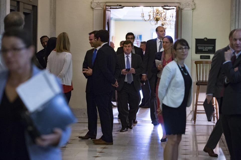 Senators and their staffers exited chambers Sunday during a brief recess at the State House.