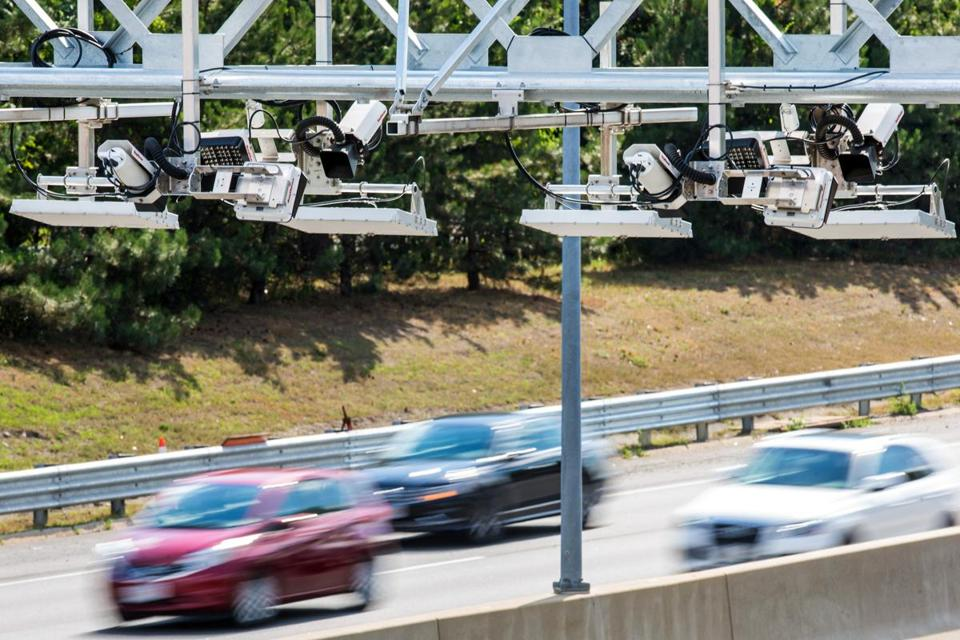 Cars whizzed by a Mass. Pike toll gantry in Newton.