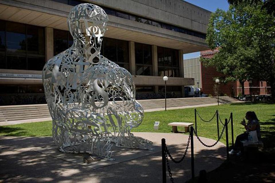 "A woman eats lunch next to the ""Alchemist"" sculpture by Jaume Plensa at the Massachusetts Institute of Technology (MIT) campus in Cambridge, Massachusetts, U.S., on Tuesday, June 30, 2015. Massachusetts Institute of Technology, founded in 1861, is traditionally known for its research and education in the physical sciences and engineering, and more recently in biology, economics, linguistics, and management as well. Photographer: Victor J. Blue/Bloomberg via Getty Images"