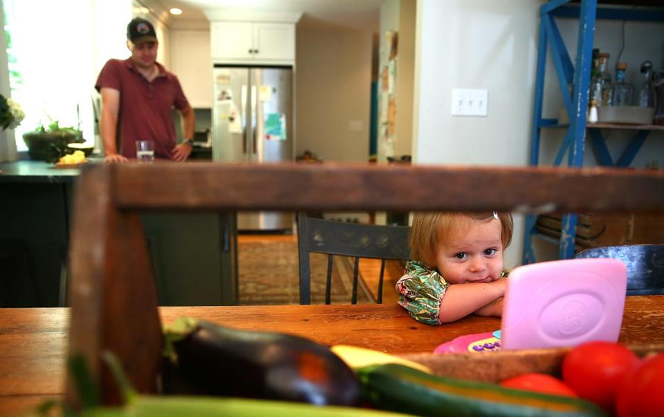 Nina Bagby, 1, who had an elevated lead level, hangs out in the kitchen of her family's home with her dad close by.