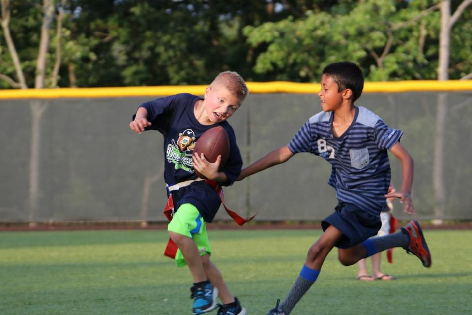 Ben Cimorelli dodges a flag-grab by 8-year-old Ziyaad Olla during a flag football game in Northborough.