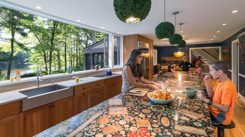 Homeowner Jill Guzzi offers Spencer a snack at the island that runs parallel to a stretch of counter overlooking a pond. The sink is hammered metal. Guzzi knew she wanted a large window, but had no idea how spectacular the result would be.