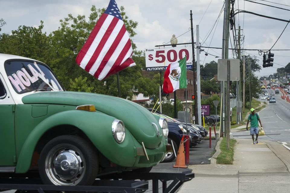 A pedestrian walked in front of a used car lot that is flying both the Mexican and American flags along Buford Highway in Norcross, Ga., late last month.