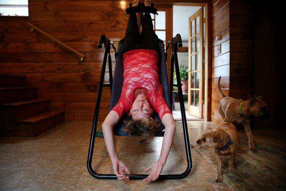 Barbara deJager used an inversion board to stretch her spine at her home in South Hamilton, Mass.