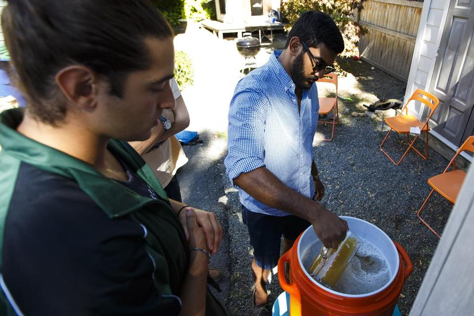 Teryn Citino (left) and Prakash Iyer filtered their beer during the brewing process.