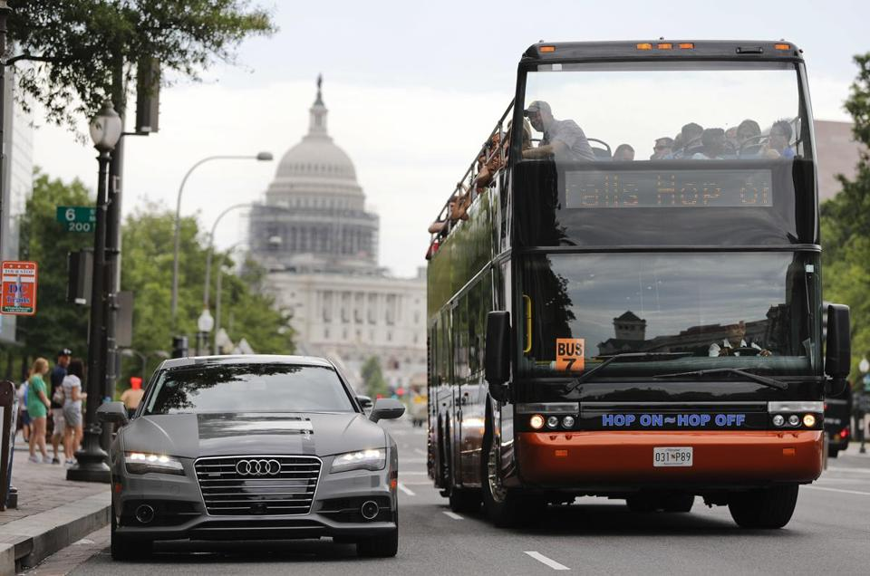 A bus drove by an Audi self-driving vehicle parked on Pennsylvania Avenue near the Capitol in Washington.
