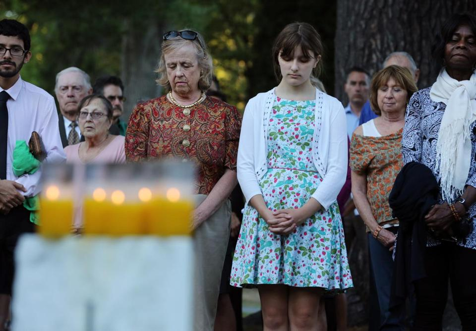 Photo: Craig F. Walker / Globe Staff. Sandy Downes, (center left) and her granddaughter, Abby Files, 14, of Milton, took part in a prayer during an interfaith vigil at the Holocaust Memorial in Milton Cemetery.