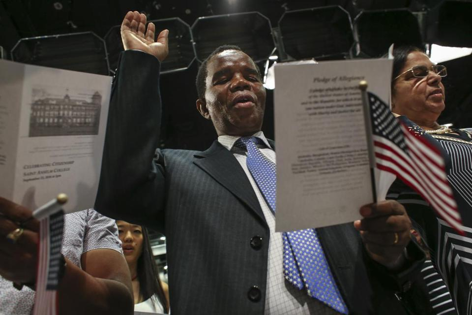 Adison Soko of Derry, N.H., formerly of Zimbabwe, raised his hand for an oath during a citizenship ceremony at the New Hampshire Institute of Politics at Saint Anselm College.