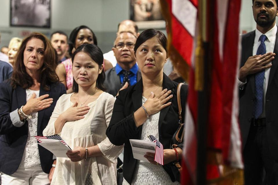 Hong Mei Zhai (center) of Derry, N.H., formerly of China, said the Pledge of Allegiance at a recent citizenship ceremony.