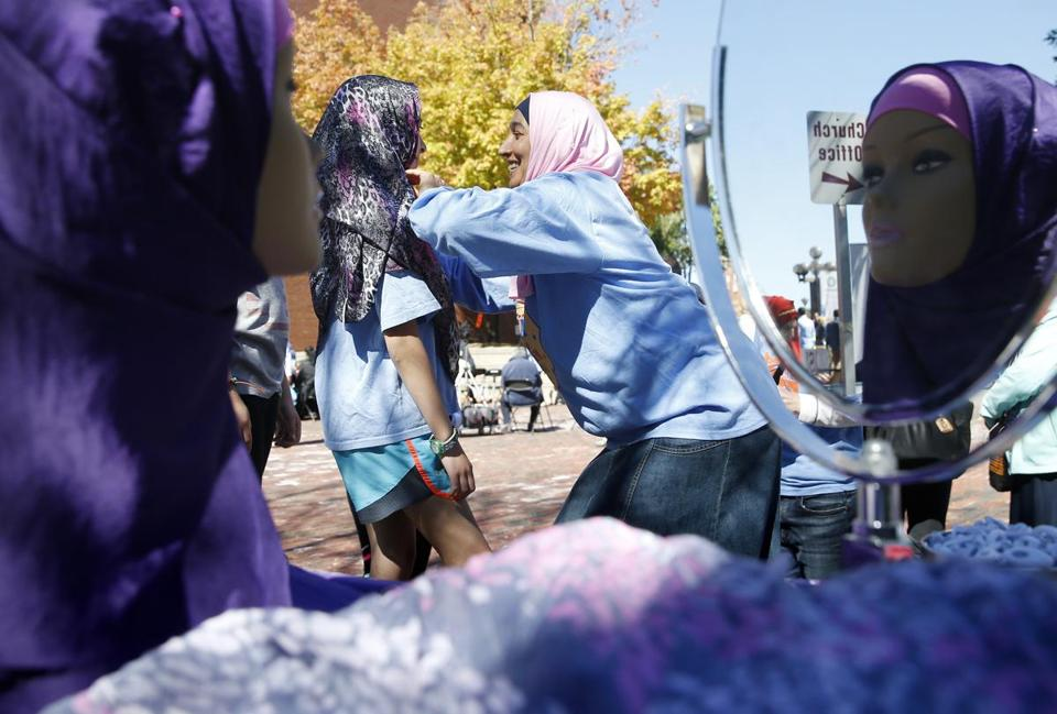Halima Benmansour helped a visitor try on a hijab during the festival in Malden.